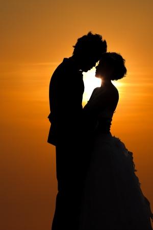 couple enlac�: Coucher de soleil silhouette d'un jeune couple embrassant Banque d'images
