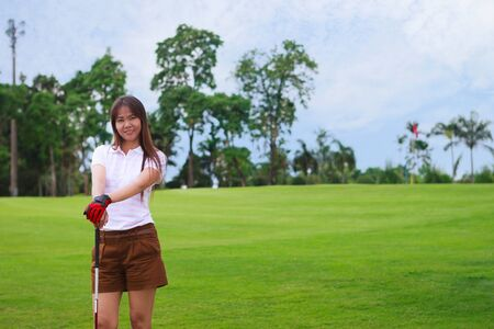 Young girl golfer standing near green at golf course photo