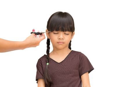 Cutting the hair of a little girl, Isolated on white photo