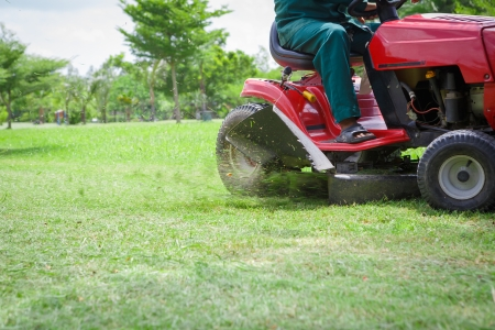 Lawnmower cutting overgrown grass