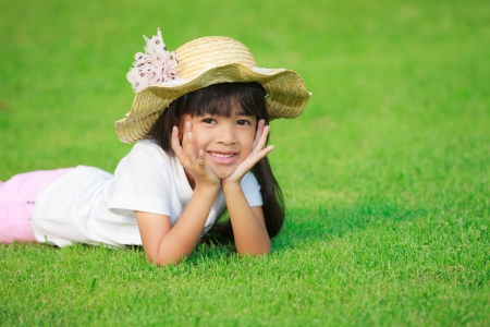 Portrait of a smiling little girl lying on green grass photo
