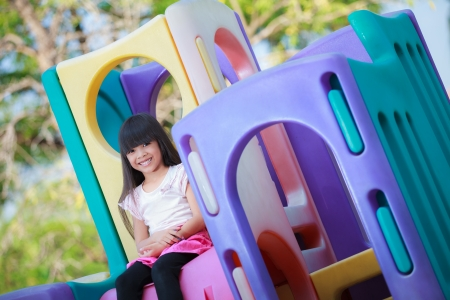 Smiling asian little girl sitting on children playground photo