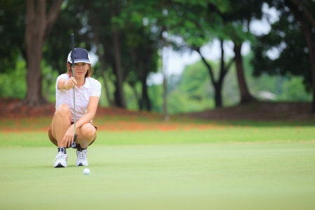 putting green: Female golf player with putter squatting to analyze the green at golf course
