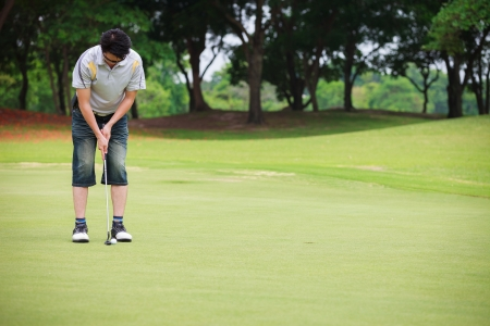 Asian man putting on golf course photo