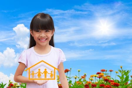 familias jovenes: Niña sonriente que muestra el símbolo de la familia con cielo de fondo agradable