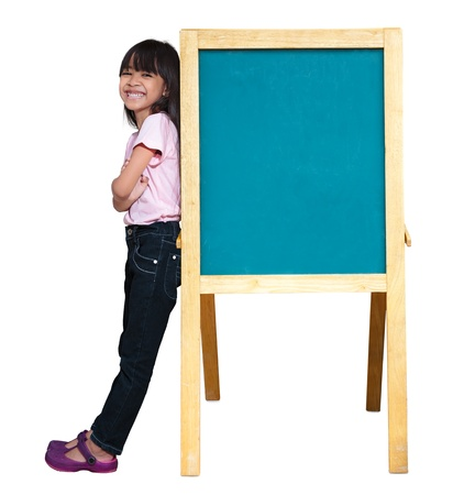 Smiling little girl standing beside a blackboard, Isolated on white photo