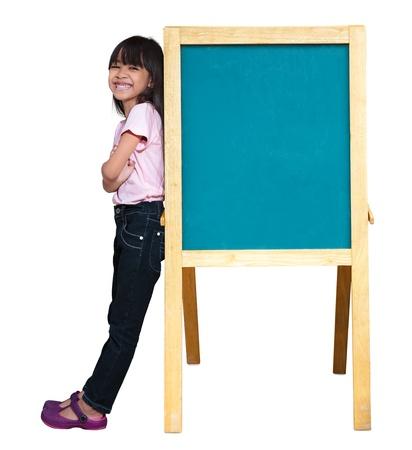 Smiling little girl standing beside a blackboard, Isolated on white Stock Photo - 14232058
