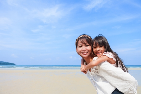 asian family outdoor: Mother having daughter a piggyback at the beach