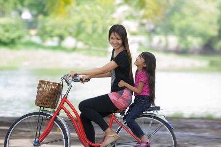 cycleway: Madre e figlia in bicicletta una bicicletta al parco Archivio Fotografico