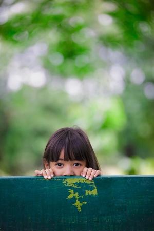 ni�os jugando en el parque: La ni�a estaba escondido detr�s de una silla en el parque, retrato al aire libre