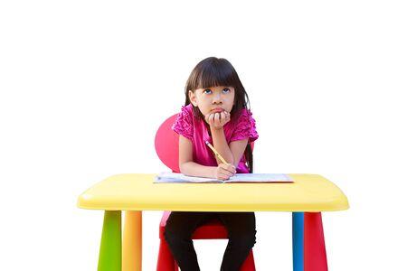 Sorridente bambina scrittura sulla scrivania, isolato su bianco