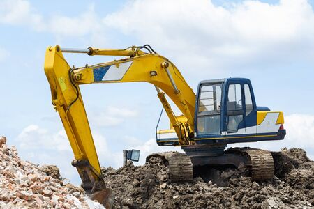 sand quarry: Backhoe standing in sandpit with over cloudscape sky