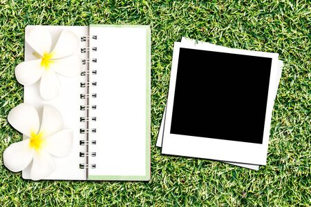 Photo frame and notebook on green grass background photo