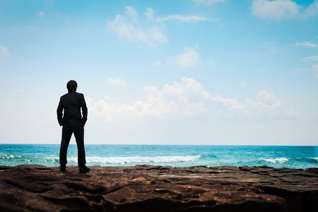 blue sky thinking: Portrait young business man in suit face to the sea