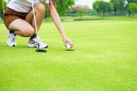 putting up: Close up of female golf player picking up ball from hole at green Stock Photo