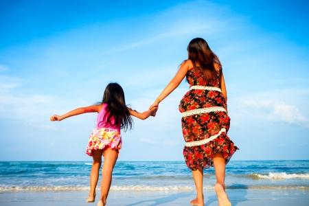 hija: Madre y su hija corriendo juntos tomados de la mano mientras en la playa Foto de archivo