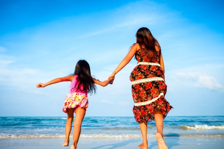 Mother and her daughter running together while holding hands on beach photo