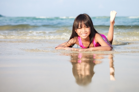 thai teen: Smiling little girl laying in water on the beach
