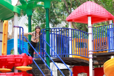 Smiling asian little girl is playing on children playground photo