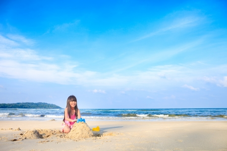 Asian little girl playing sand on the beach