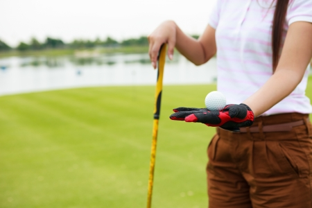 Woman golf player showing golf ball holding golf club photo