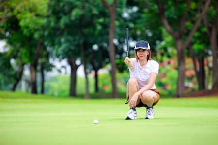 to crouch: Female golf player with putter squatting to analyze the green at golf course