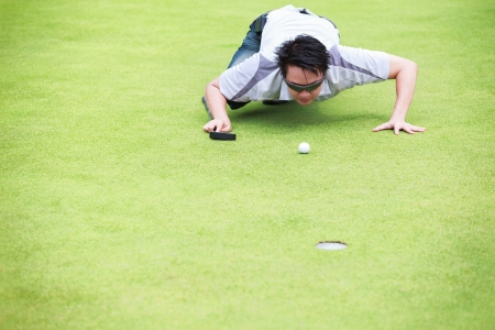 Golfer checking line of putt on green photo