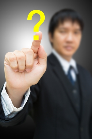 risks icon: Business man pressing on Question mark Stock Photo