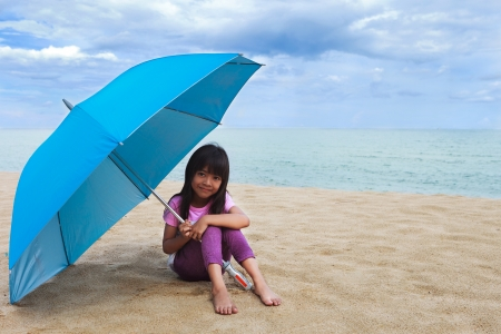 Smiling little girl sitting at beach and umbrella with blue sky photo