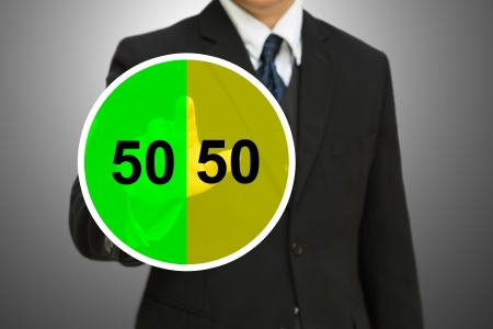Business man touching on Pie chart with fifty-fifty percent  50 50 chance photo