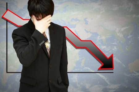 Stressed businessman with low financial graph of global business Stock Photo