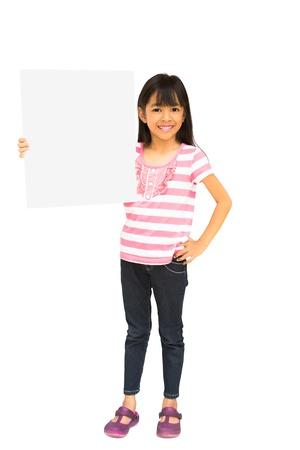 ni�os sosteniendo un cartel: Sonriente ni�a asi�tica que sostiene la muestra en blanco, aislados en blanco con trazado de recorte Foto de archivo