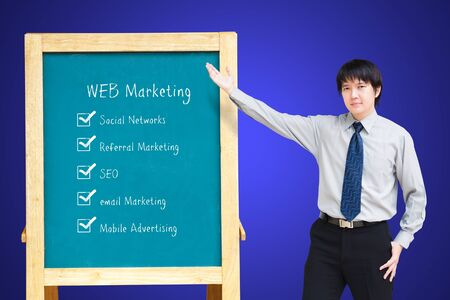 Asain business man presenting WEB Marketing plan on a chalkboard photo