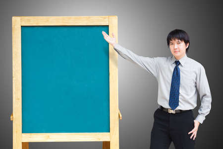 Asian business man showing blank chalkboard photo