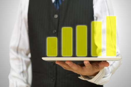 Business man holding Holographic bar graph on tablet pc Stock Photo