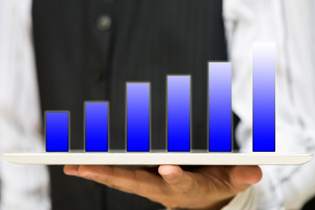 Business man holding Holographic bar graph on tablet pc photo