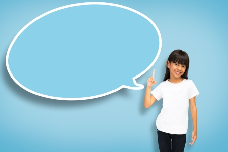 Smile asian little girl with blank speech bubble on blue background photo