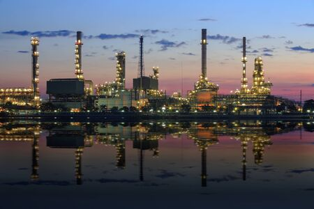 Refinery plant area at twilight with reflection in river photo
