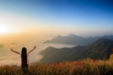 looking at view: Piccola ragazza in piedi in cerca di mare, nebbia in montagna Archivio Fotografico