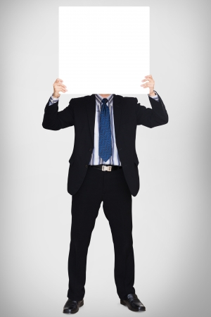 Business man in dark suit holding a blank sign over grey background Stock Photo - 16331438