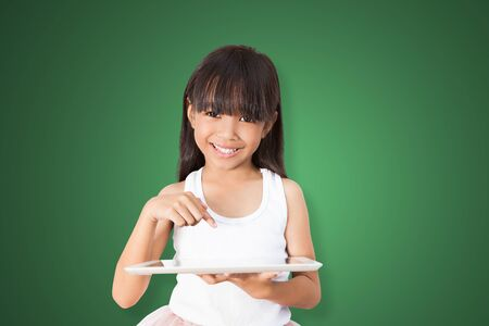 asian children: Asian girl using tablet PC over green background with clipping path