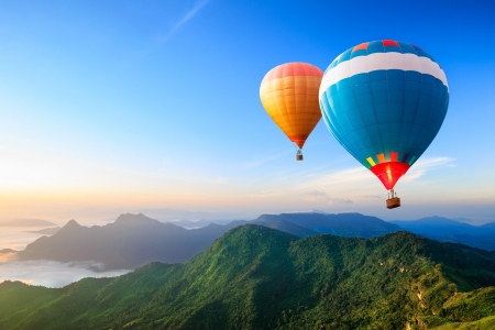 viagem: Coloridos balões de ar quente sobrevoando a montanha Banco de Imagens