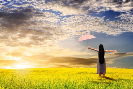 Asian girl holding pink umbrella in grass field and sunset