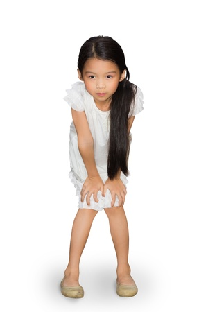 Asian little girl standing with hands on knees, Isolated over white  photo