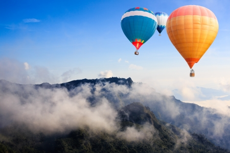 ballooning: Colorful hot-air balloons flying over the mountain Stock Photo