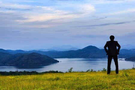 Businessman standing on a green grass in the mountains photo