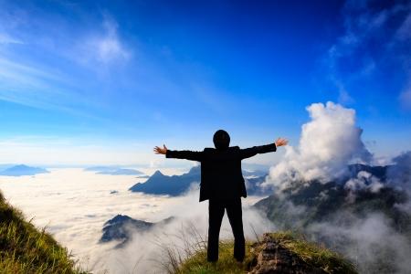 lideres: Empresario de pie sobre un césped verde en las montañas Foto de archivo