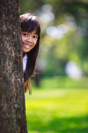 eye protection: Portrait of asian little girl smiling behind a tree Stock Photo
