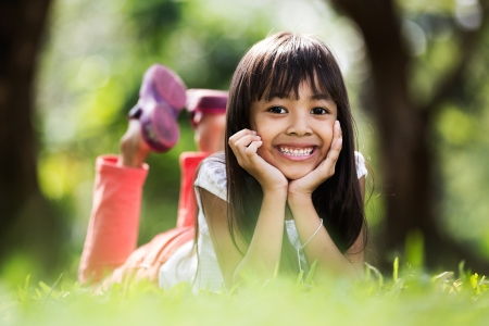 Asian little girl laying on green ground
