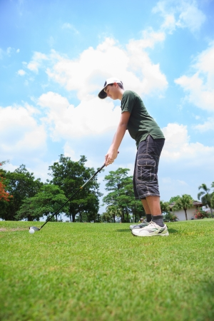 Young male golf player at the course ready to hit the ball photo